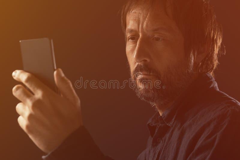 看流动手机屏幕的成人人 免版税库存照片