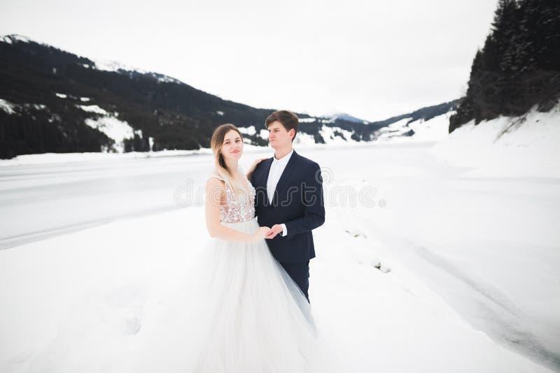 看浪漫年轻的夫妇,后面视图、湖和冬天山在背景 免版税库存照片