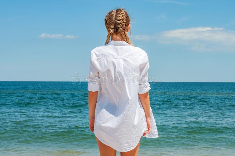 看海洋,海滩的白色衬衣的美丽的被晒黑的妇女 免版税库存图片