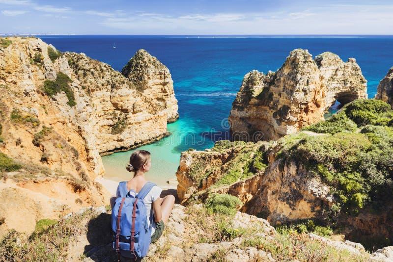 看海的年轻女人旅客在拉各斯镇,阿尔加威地区,葡萄牙 旅行和活跃生活方式概念 免版税库存照片