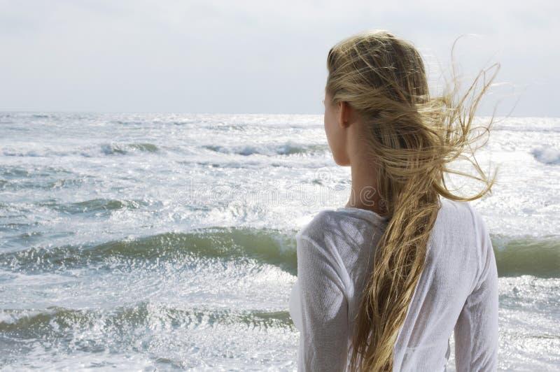 看海洋的白肤金发的妇女 免版税库存照片