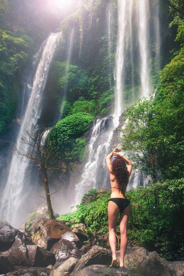 看瀑布的年轻性感的妇女在密林 生态旅游 免版税图库摄影