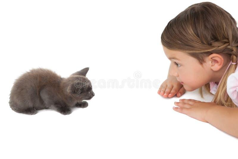 看灰色小猫的逗人喜爱的小女孩说谎在地板上 免版税库存图片