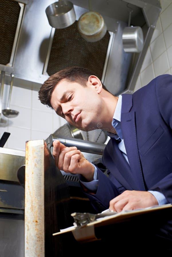 看烤箱的健康审查员在商业厨房里 免版税库存图片