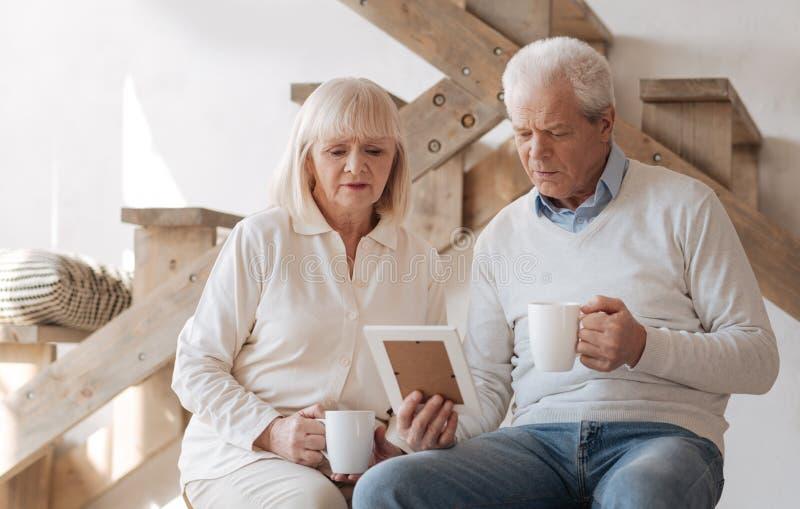 看照片的哀伤的年长夫妇 免版税库存图片