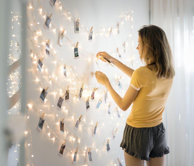 看照片的妇女垂悬与装饰在白色墙壁上点燃 免版税图库摄影
