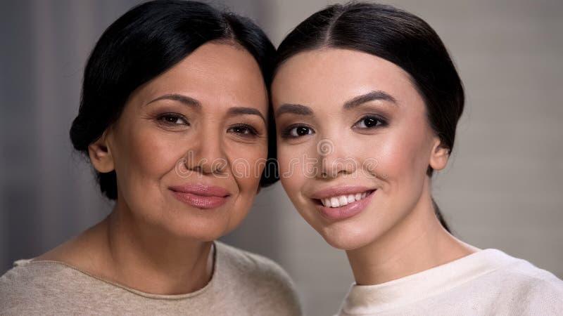 看照相机、母亲和女儿面孔特写镜头的两名微笑的亚裔妇女 免版税库存照片