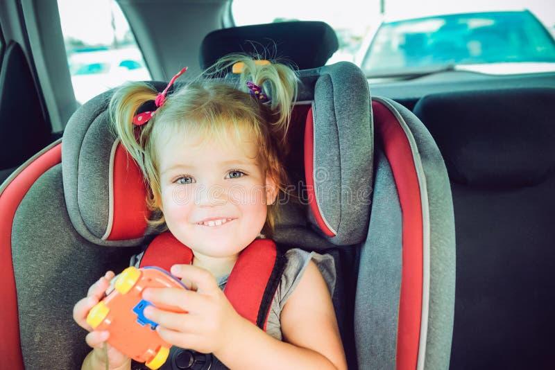 看照相机和坐在微型汽车位子的微笑的小blondy女孩画象  孩子紧固与在安全的安全传送带 图库摄影