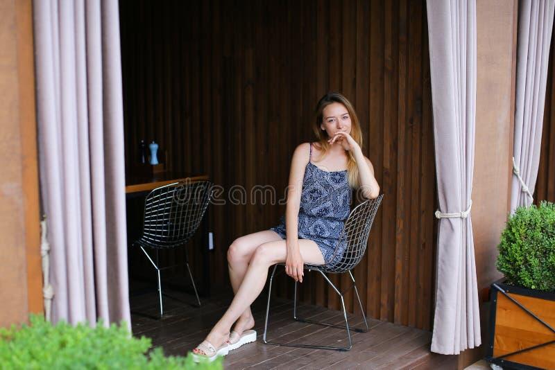 看照相机和微笑在与关闭的咖啡馆附近的少妇 免版税库存照片