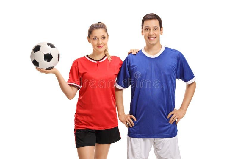 看照相机和微笑的女性和男性足球运动员 免版税库存图片