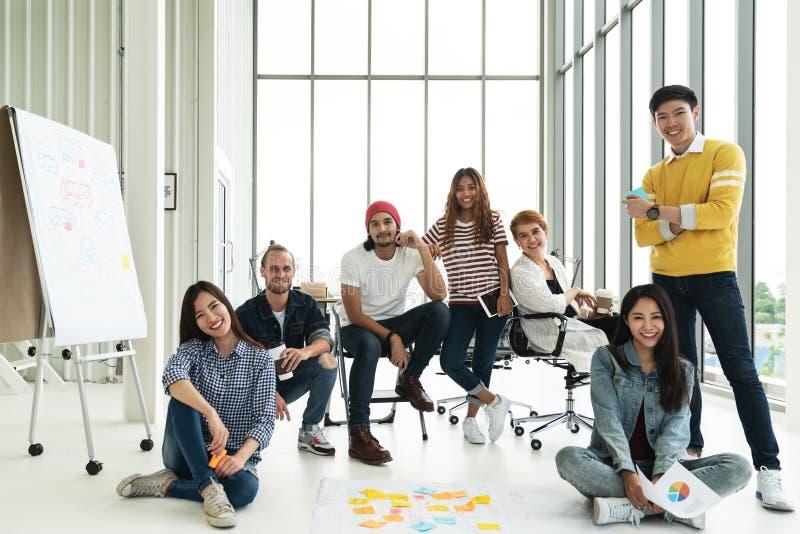 看照相机和微笑的愉快的不同的创造性的企业队小组画象  库存照片