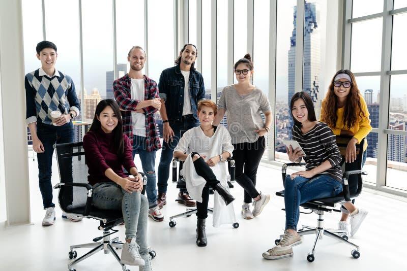 看照相机和微笑的愉快的不同的创造性的企业队小组画象  图库摄影