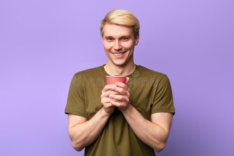 看照相机和拿着塑料杯子的正面愉快的年轻帅哥 免版税库存照片