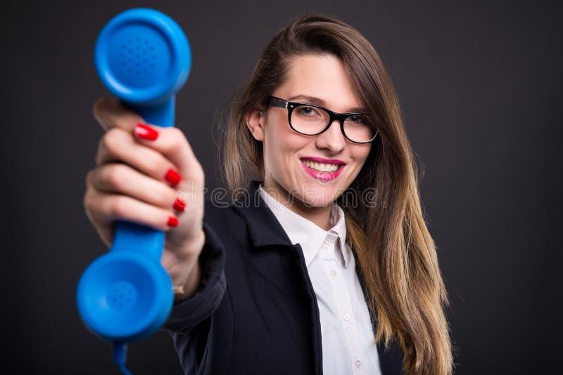 看照相机和拿着电话的年轻女实业家 免版税库存图片
