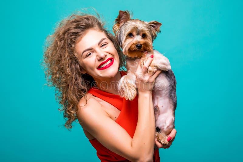 看照相机和拿着约克夏狗的微笑的年轻可爱的妇女画象隔绝了在绿色背景的看法 库存图片