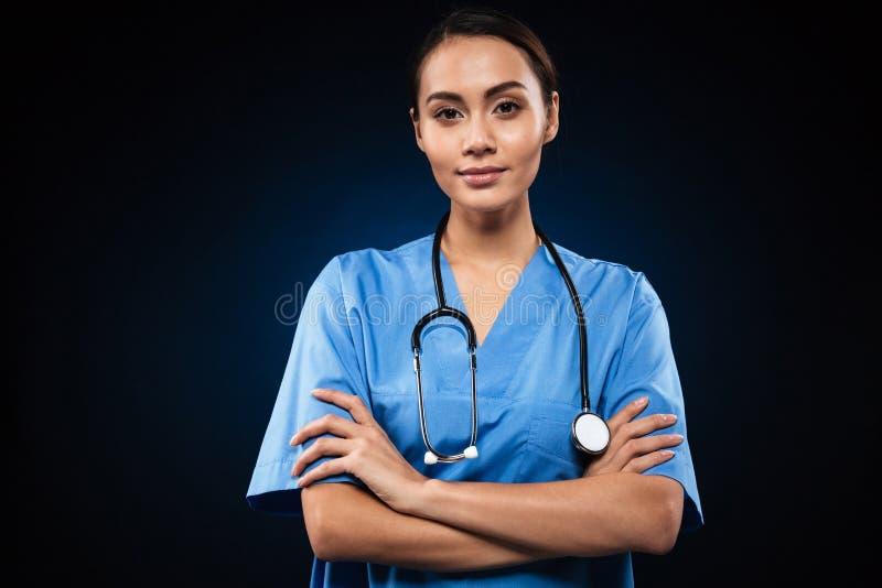 看照相机和握手的严肃的女性医生折叠了隔绝 免版税库存图片