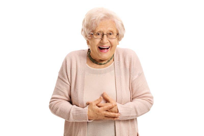 看照相机和笑的惊奇的年长妇女 图库摄影
