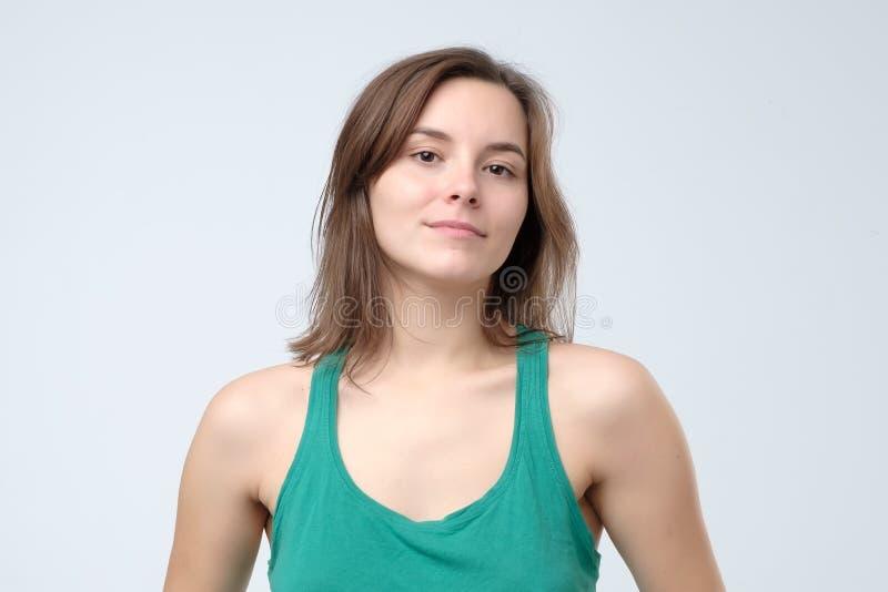 看照相机微笑的快乐的愉快的年轻美女 免版税库存图片