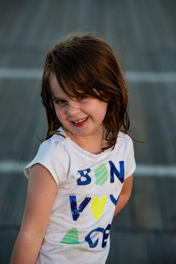 看照相机微笑的木板走道的年轻逗人喜爱的小女孩 免版税图库摄影