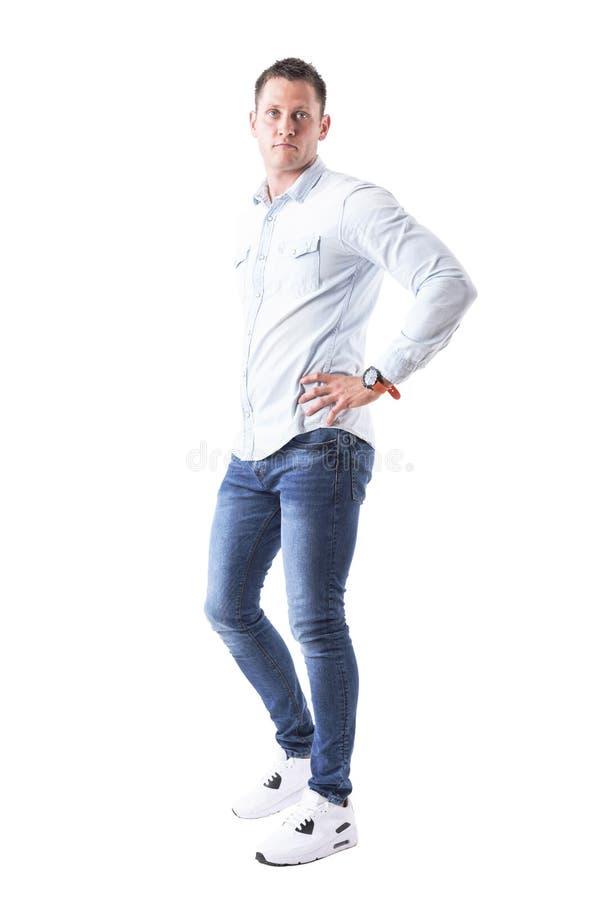 看照相机用在臀部的手的浅兰的衬衣的英俊的年轻成人白种人蓝眼睛的人 免版税库存照片