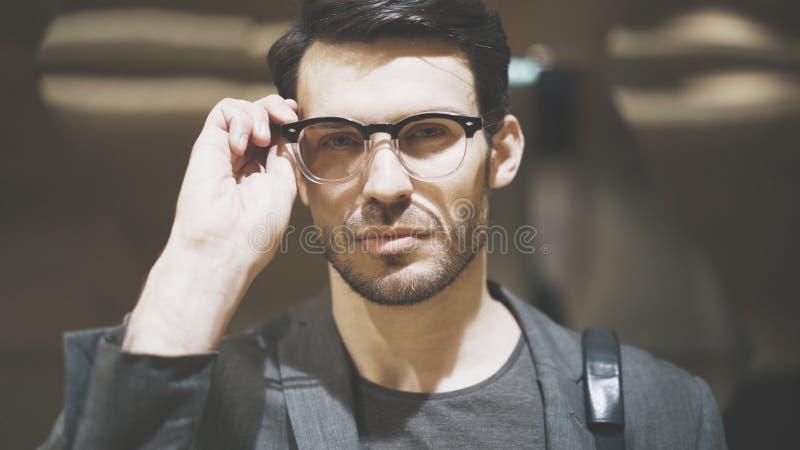 看照相机的一个年轻有胡子的人的特写镜头 库存图片