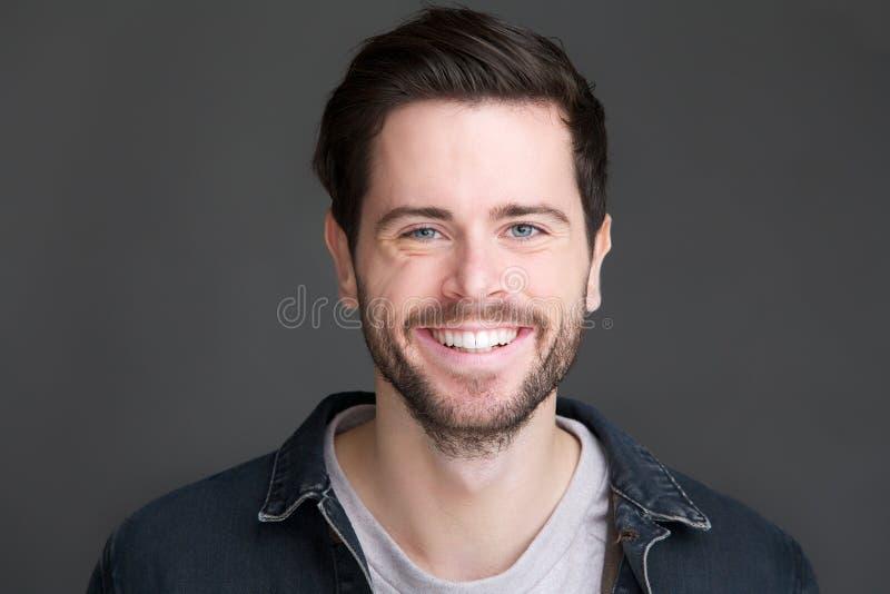 看照相机的一个微笑的年轻人的画象 免版税库存图片