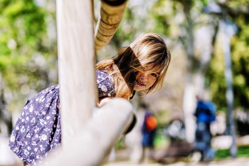 看照相机的一微笑的女孩的正面图在公园在一好日子 库存照片
