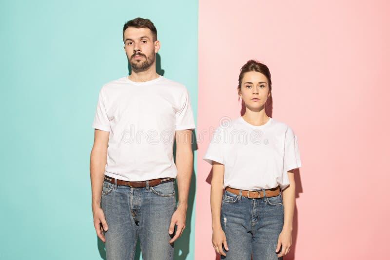 看照相机的严肃的男人和妇女反对桃红色和蓝色背景 图库摄影