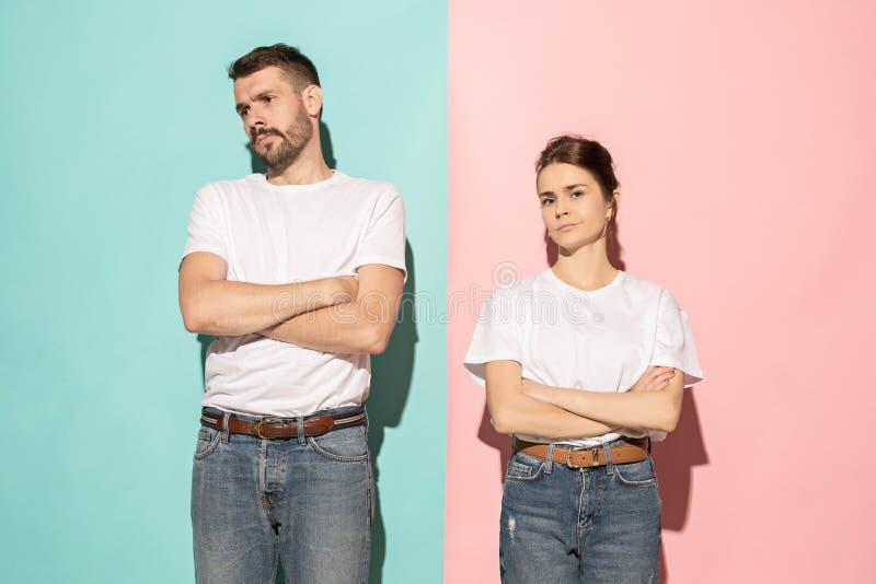 看照相机的严肃的男人和妇女反对桃红色和蓝色背景 免版税图库摄影