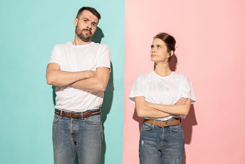 看照相机的严肃的男人和妇女反对桃红色和蓝色背景 库存图片