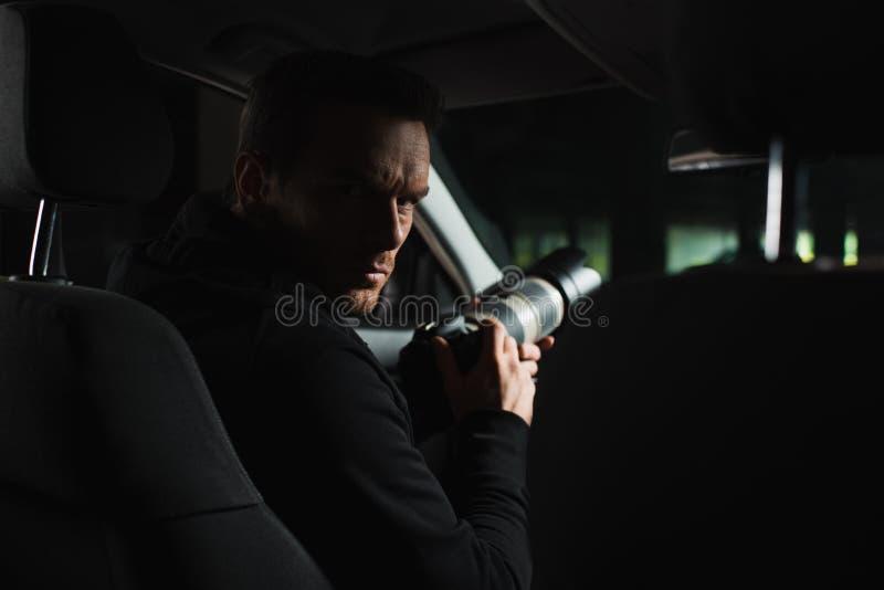看照相机的严肃的男性无固定职业的摄影师,当做监视时 图库摄影