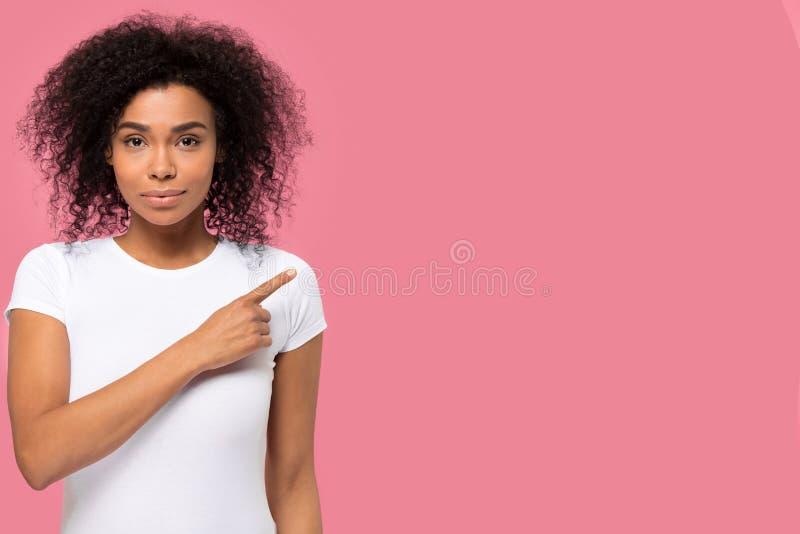 看照相机的严肃的确信的非洲妇女指向手指在旁边 免版税库存照片