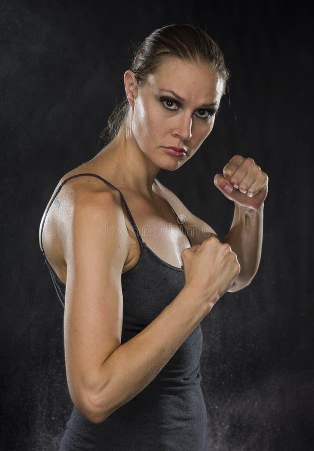 看照相机的作战姿势的坚强的妇女 图库摄影