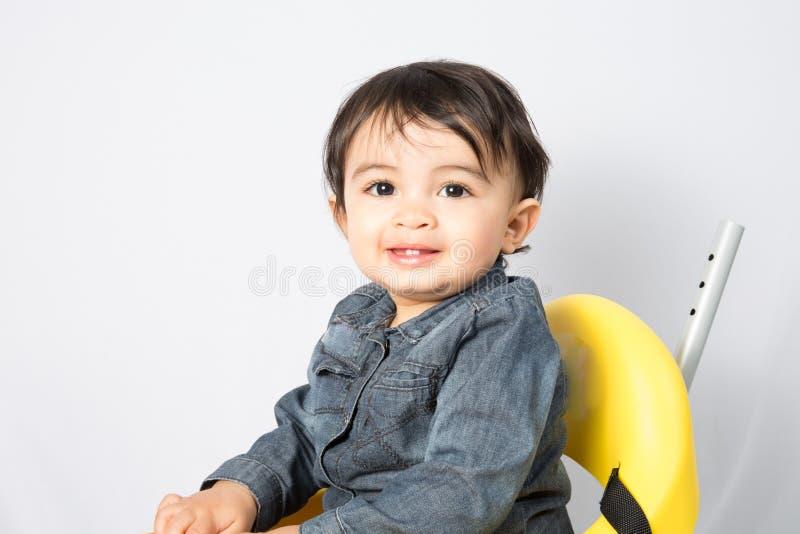 看照相机的可爱的年轻愉快的男孩坐玩具汽车 免版税库存照片