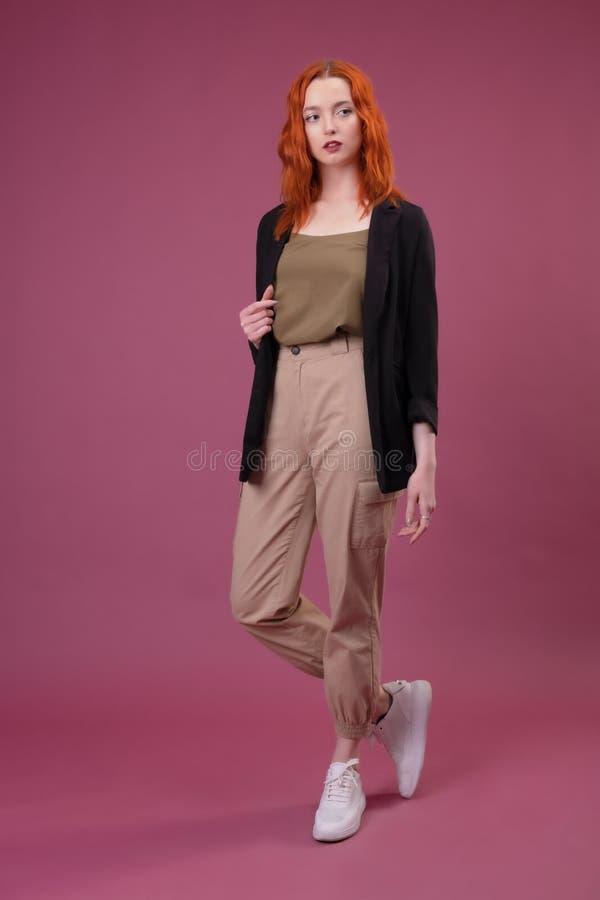 看照相机的可爱的年轻红头发人妇女 图库摄影