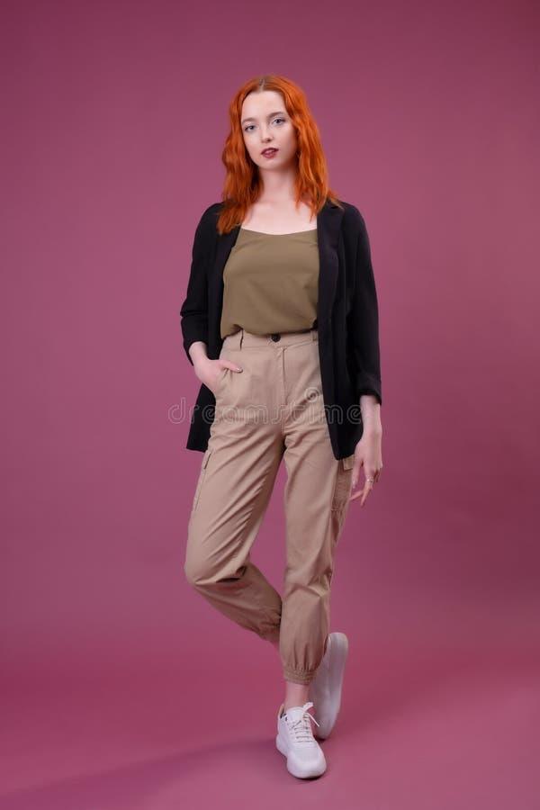 看照相机的可爱的年轻红头发人妇女 免版税库存图片