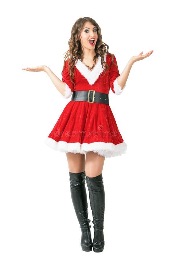 看照相机的吃惊的圣诞老人妇女传播的胳膊 免版税图库摄影