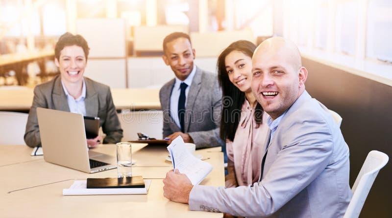看照相机的四位企业专家在会议期间 免版税库存图片
