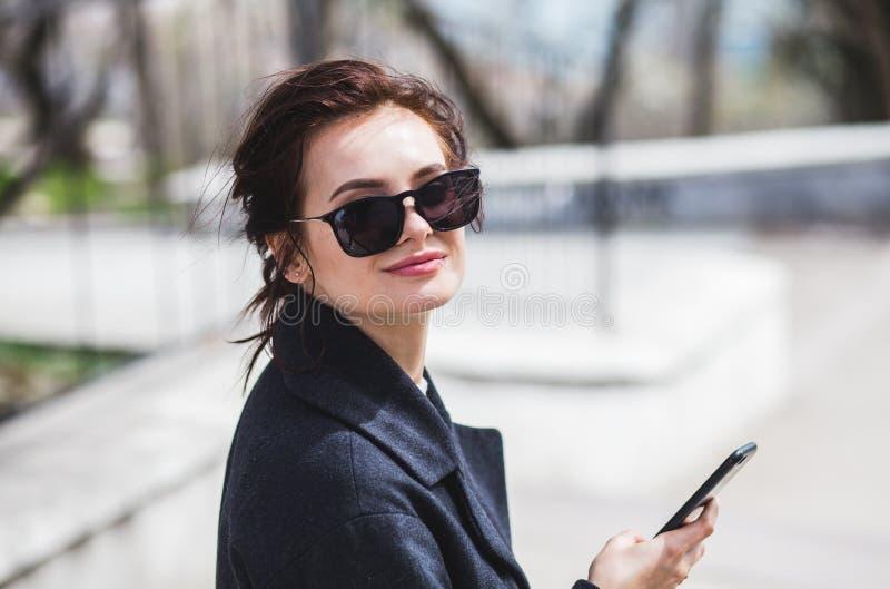 看照相机的太阳镜的年轻时髦的美丽的深色的女孩拿着她的在街道的智能手机在春天 免版税图库摄影