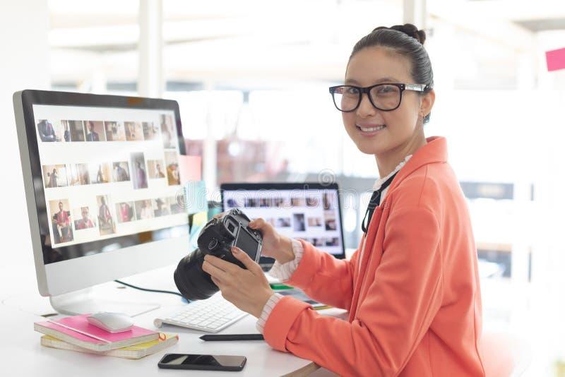 看照相机的女性图表设计师,当工作在书桌时 免版税图库摄影