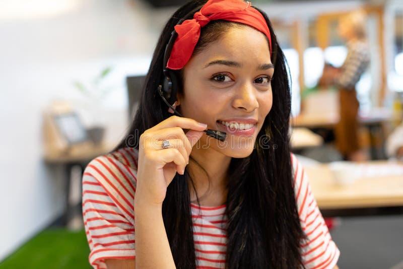 看照相机的女性客服执行委员,当谈话在耳机在一个现代办公室时 库存照片