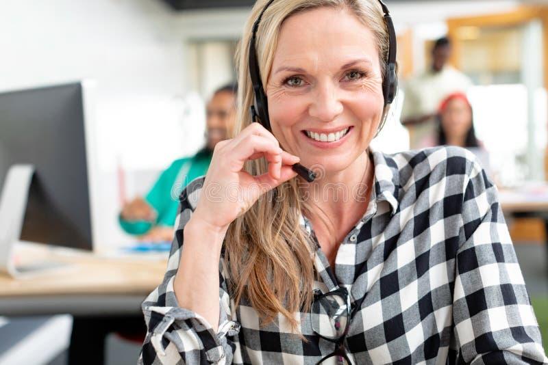 看照相机的女性客服执行委员,当谈话在耳机在一个现代办公室时 免版税图库摄影