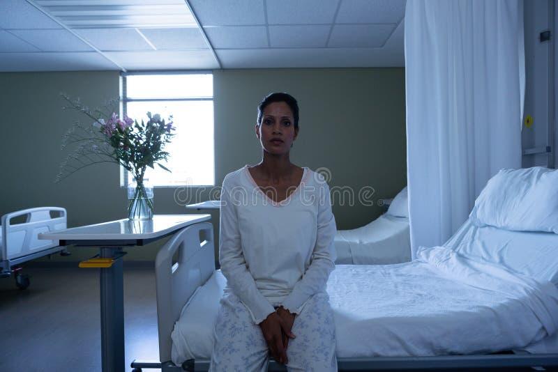 看照相机的女性患者,当坐床时 免版税库存照片