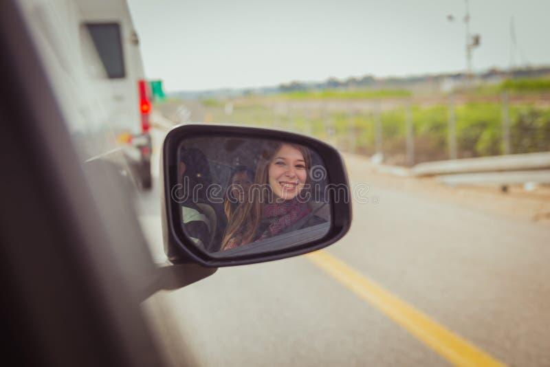 看照相机的妇女通过汽车侧视图镜子 免版税库存图片