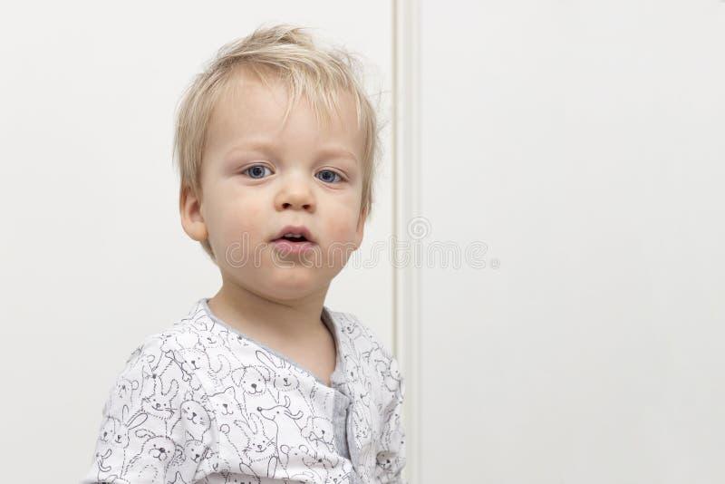 看照相机的嬉戏的被弄乱的逗人喜爱的婴孩反对白色背景 复制空间 免版税库存照片