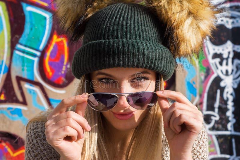 看照相机的帽子和太阳镜的滑稽的年轻白肤金发的妇女 图库摄影