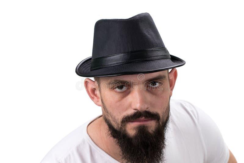 看照相机的帽子的严厉有胡子的人隔绝在白色ba 库存图片