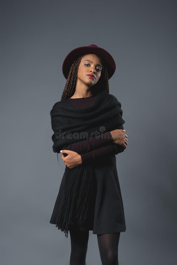看照相机的帽子的美丽的时髦的年轻非裔美国人的妇女 库存照片
