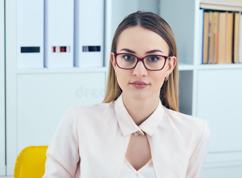 看照相机的年轻严肃的女实业家画象,当使用膝上型计算机在办公室时 库存照片
