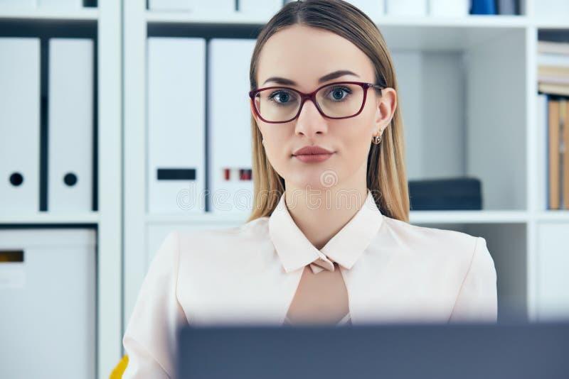 看照相机的年轻严肃的女实业家画象,当使用膝上型计算机在办公室时 免版税库存照片